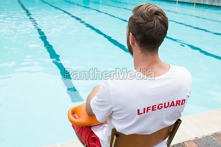 rettungsschwimmer sitzt am strand mit rettungsboje