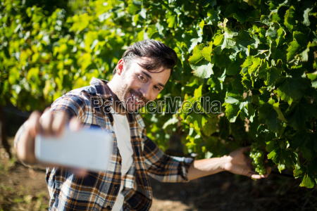 happy man taking selfie with grapes