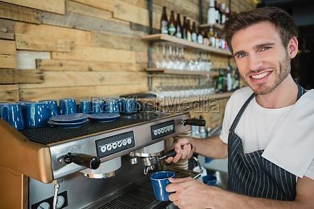 portrait of smiling waiter preparing coffee