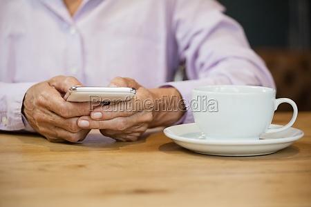 midsection der aelteren frau mit smartphone