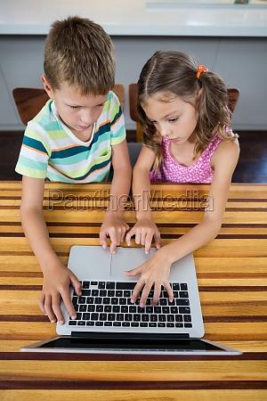 geschwister die laptop in der kueche