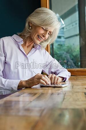 smiling senior woman using smart phone