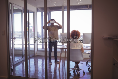 female colleague with businessman wearing vr