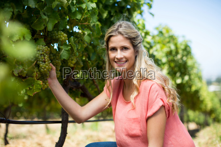 portrait of smiling woman holding grapes