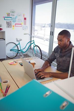 businessman using laptop on desk in
