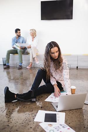 businesswoman using laptop on floor at