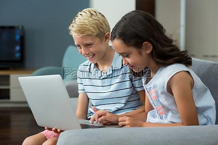 laechelnde geschwister die laptop im wohnzimmer