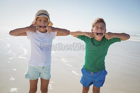 geschwister machen necken gesichter am strand