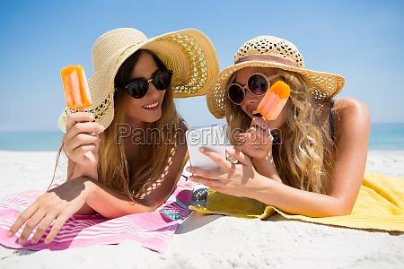 freundinnen die intelligentes telefon beim essen
