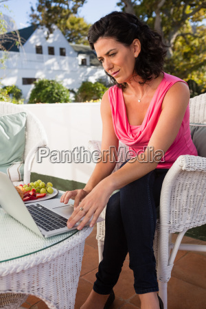 mid adult woman using laptop at