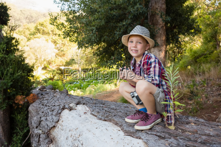 smiling boy sitting on the tree
