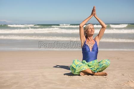 senior frau ueben yoga beim sitzen