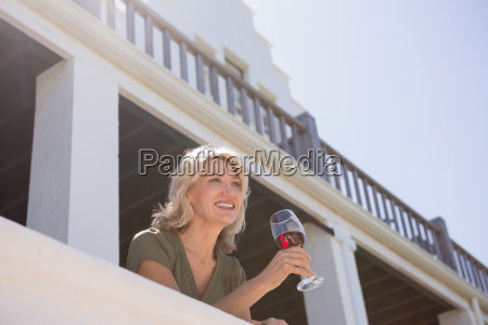 blond woman holding red wineglass in