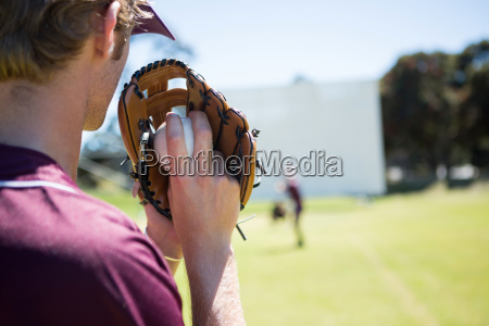 baseball pitcher holding ball in glove