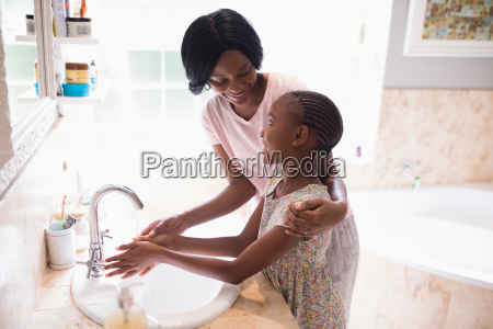 mother and daughter washing hands at