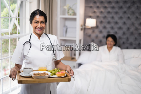 nurse holding breakfast tray while patient