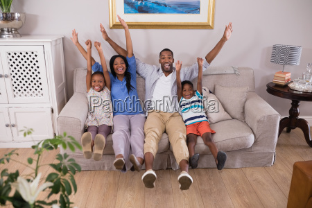 happy family cheering while sitting on