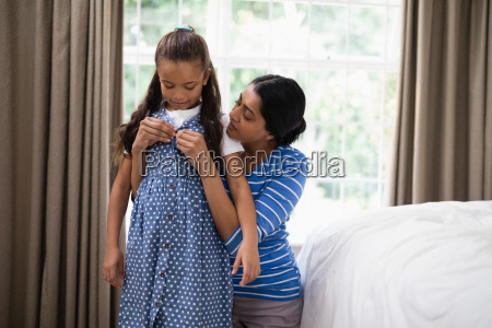 mother helping daughter to dress up