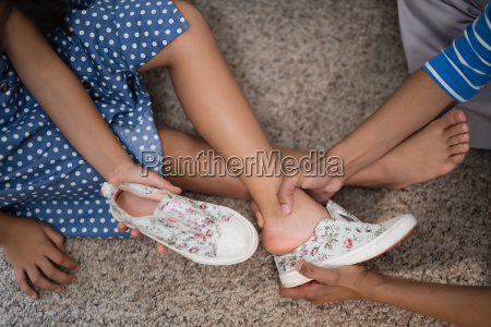 cropped image of mother helping daughter