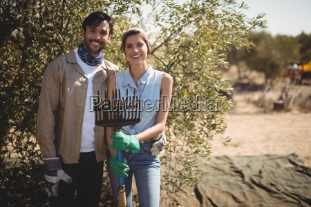 smiling young couple holding rake at