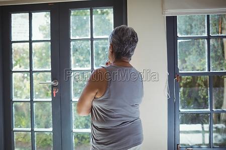 thoughtful senior woman looking through window