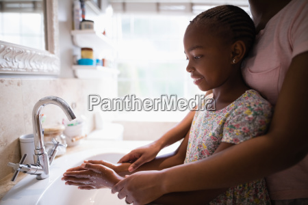 mother assisting daughter while washing hands