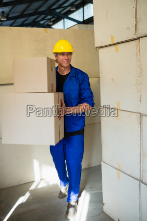 worker holding a cardboard boxes while