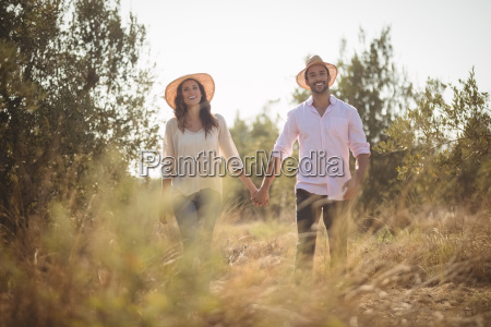 smiling young couple holding hands at