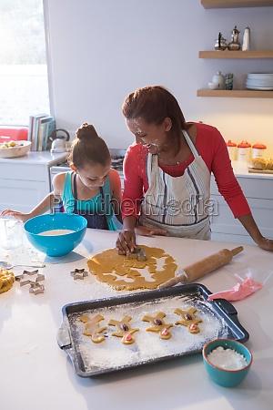 mother and daughter preparing cookies in