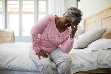 tense senior woman sitting on bed