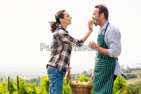 woman feeding apple to man at