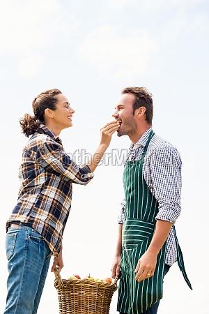 smiling woman feeding apple to man
