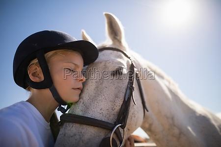 reitermaedchen welches das pferd umfasst