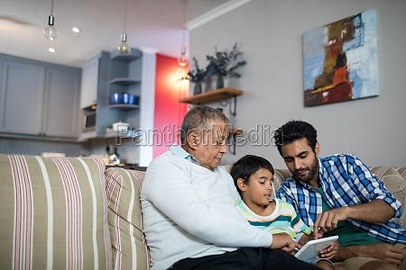 vater und grossvater zeigen auf tablette