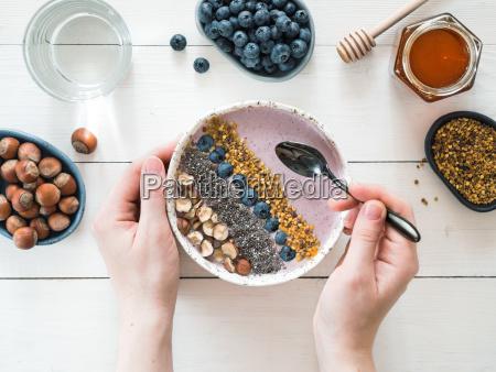 fruehstuecksschuessel in den frauenhaenden