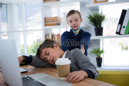 boy as business executive sleeping while