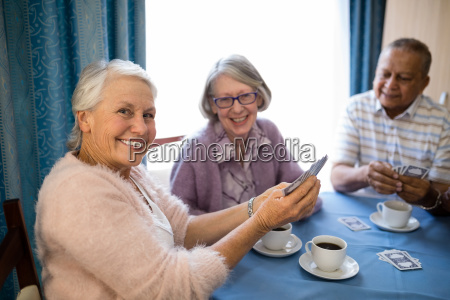 smiling senior friends playing cards while