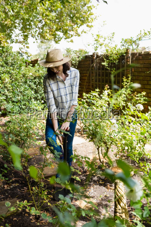smiling woman shoveling in the garden