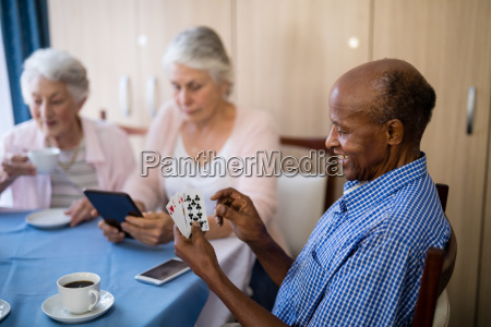 senior man playing cards with friends
