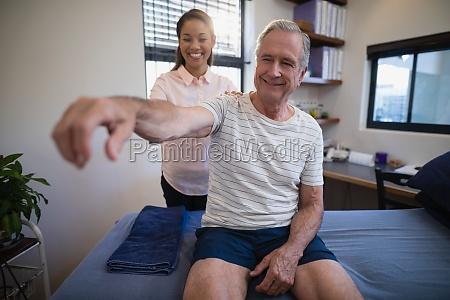 smiling female doctor examining shoulder of