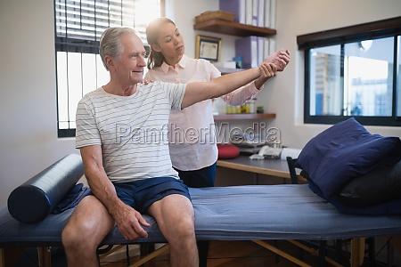 female doctor examining wrist of senior