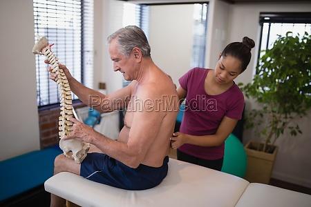 female therapist examining back of shirtless