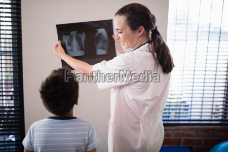 smiling female doctor showing x ray
