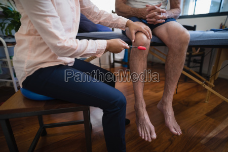 low section of female therapist examining