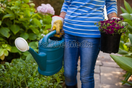 midsection of senior woman holding watering