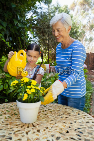 smiling senior woman standing by granddaughter