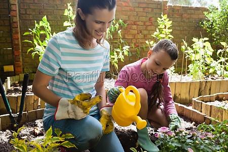 cheerful mother kneeling by girl watering