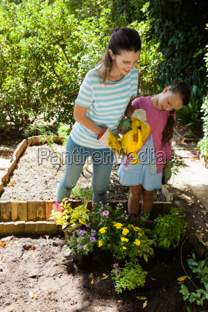 smiling woman and daughter watering flowers