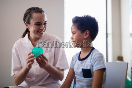 smiling female therapist showing stress ball