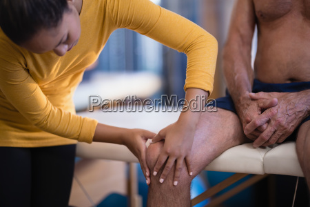 female therapist massaging knee of senior